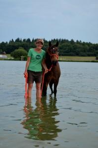 Jeune fille et son poney, les pieds dans un étang
